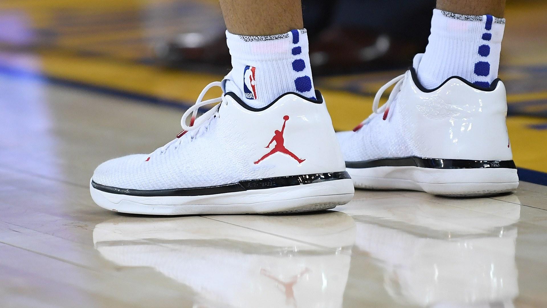 Tenis blancos de la marca JOrdan sobre una duela de NBA
