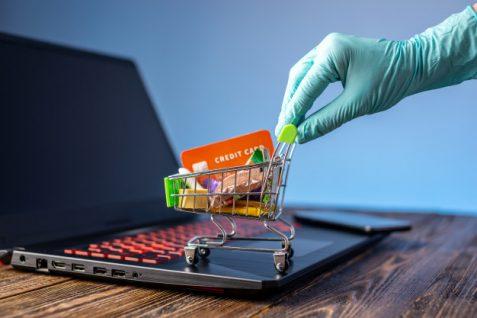 Mano sostiene carrito de compras y tarjeta de crédito